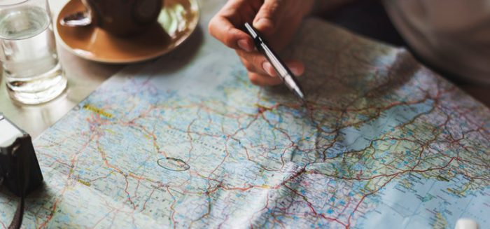 Man making travel and budgeting plans on a map